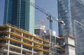 Two elevating cranes on a construction site — Stock Photo