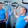 Stock Photo: Athlete man in gym with personal fitness trainer