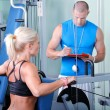Woman in gym exercise with personal fitness trainer — ストック写真