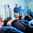 Woman in gym exercise with personal fitness trainer — Stock Photo