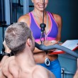 Athlete man in gym with personal fitness trainer — Foto Stock