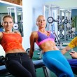 Two women in gym exercise with personal fitness trainer — Stok fotoğraf