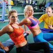 Two women in gym exercise with personal fitness trainer — Foto de Stock