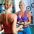 Two beautiful women exercise in gym with weights — Stock Photo