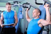 Muž sportovec v tělocvičně s osobní fitness trenér — Stock fotografie