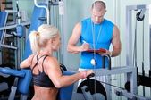 Woman in gym exercise with personal fitness trainer — 图库照片