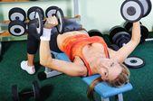 Bir spor salonunda güzel kaslı kadın egzersiz — Stok fotoğraf
