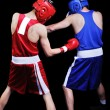 Two male boxers fighting on black background — Stock Photo