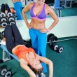 Two beautiful women exercising in gym with weights — Stock Photo #13494075