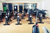 Group of spinning bicycles at fitness studio — Stock Photo