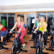 Beautiful women doing exercise in a spinning class at gym — Stock Photo #29885357