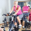Beautiful women doing exercise in a spinning class at gym — Stock Photo #29885505