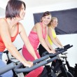 Beautiful women doing exercise in a spinning class at gym — Stock Photo #29885859
