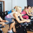 Beautiful women doing exercise in a spinning class at gym — Stock Photo #29886039