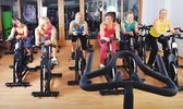Belle donne, fare esercizio in una classe di spinning in palestra — Foto Stock