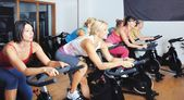 Beautiful women doing exercise in a spinning class at gym — Stock Photo