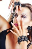Beautiful Brunette Girl with Hands over Her Face. Black Jewelry — Stock Photo