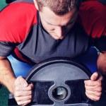 hombre musculoso ejercicio en un gimnasio — Foto de Stock   #49937059