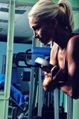 Beautiful muscular woman exercising in a gym — Stock Photo
