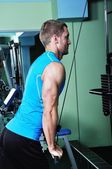 Muscular man exercising in a gym — Stock Photo