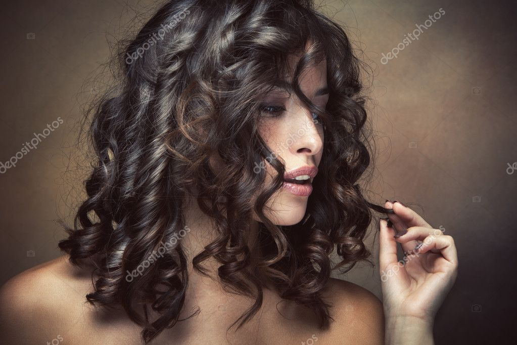 Sensual brunette woman with shiny curly silky hair studio shot — Stock Photo #12710806