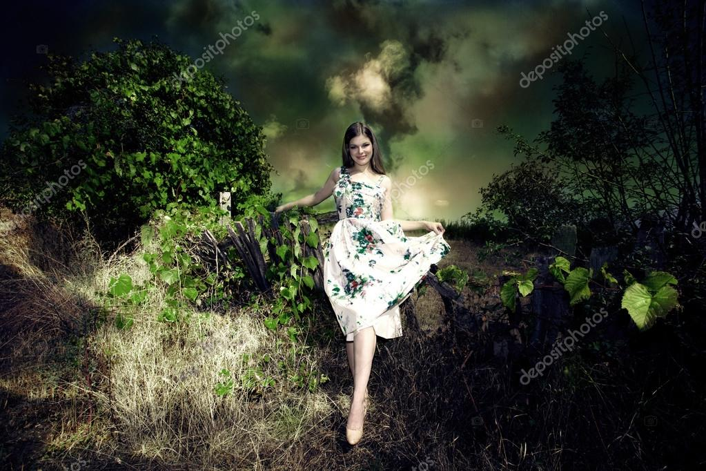 Smiling young woman fairy like in elegant dress in dark green environment — Stock Photo #13412388