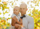 Happy young man holding a smiling 7-9 months old baby — Stock Photo