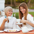 Adult mother and daughter drinking tea or coffee. They communicate sitting outside in a cafe.  — Stock Photo