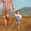 Stock Photo: Father and daughter walking on the field