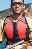 Young muscular sportsman kayaking in the sunshine — Stockfoto