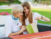 Adult mother and daughter are considering buying after shopping. They are sitting in a cafe outside. — Stockfoto