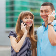 Stylishly dressed young couple talking on the phone. — Stock Photo #31164205