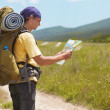 Tourist is in the mountains and see the map — Stock Photo