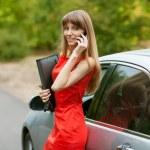 mujer de negocios elegante en un vestido rojo de pie frente a su ca — Foto de Stock