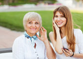 Adult mother and daughter listening to MP3 player while sitting — Stock Photo