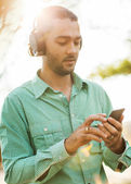 Guy listening to player in park — Stock Photo