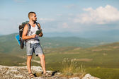 Camper is in the mountains with a map, enjoy the scenery — Stock Photo
