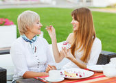 Senior mother and young attractive daughter eating cake, drinkin — Stock Photo