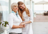 Adult mother and daughter standing at the large glass case holdi — Stock Photo