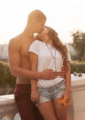 Young couple outdoor portrait. Beautiful pretty girl kissing han — Stock Photo