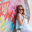 Hipster girl outdoors stands near a graffiti wall — Stock Photo