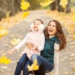 Mother and daughter in the autumn park — Stock Photo #33092407