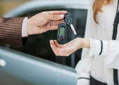 Male hand giving car key to female hand. — Stock Photo