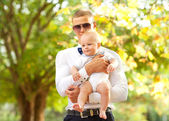 Happy young man holding baby — Stock Photo
