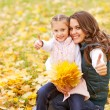 Mother and daughter playing in autumn park — Stock Photo