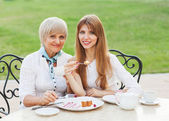 Adult mother and daughter drinking tea or coffee. — Stock Photo