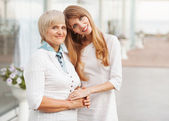 Adult mother and daughter standing at the large glass case — Stock Photo