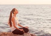 Girl in lotus pose at sunset — Stock Photo