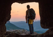 Silhouette of man with backpack in cave. Crimea. — Stock Photo