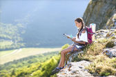 Young, beautiful girl with a backpack on her back, studying a map — Stock Photo